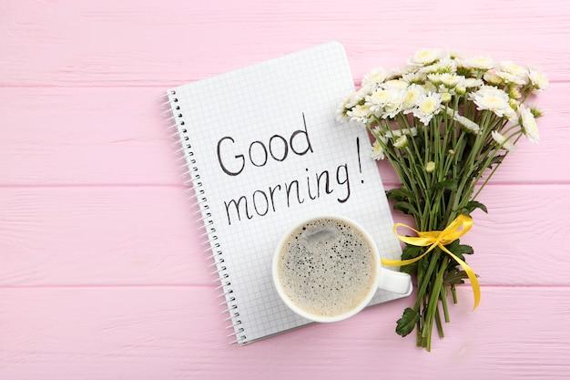 커피 한 잔의 꽃다발과 좋은 아침이라는 단어가 적힌 카드