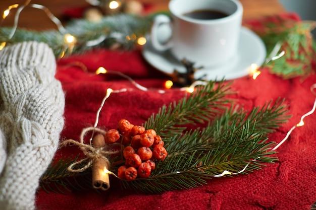 居心地の良い赤いセーターと暖かい帽子と木製のトレイにコーヒーと花輪のカップ。モミの枝と山の灰のある新年の静物
