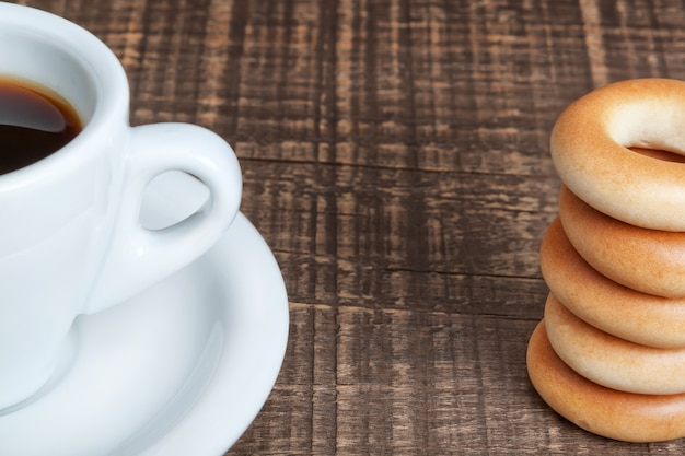 一杯のコーヒーと焼きたてのベーグルをクローズアップ。木製のテクスチャ。