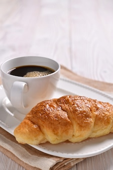 Чашка кофе и круассан на деревянный стол