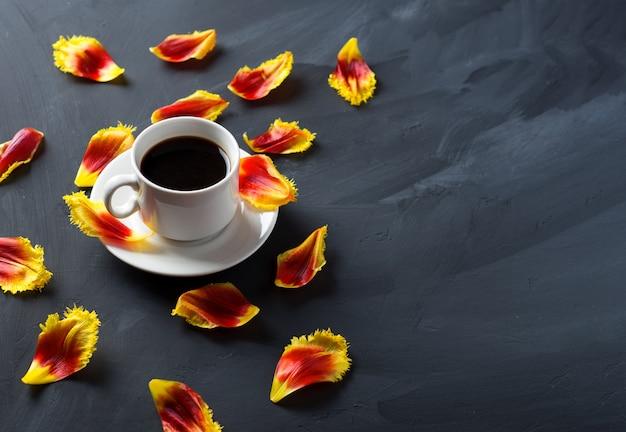 一杯のコーヒーと石のテーブルの上に散らばったチューリップの花びら