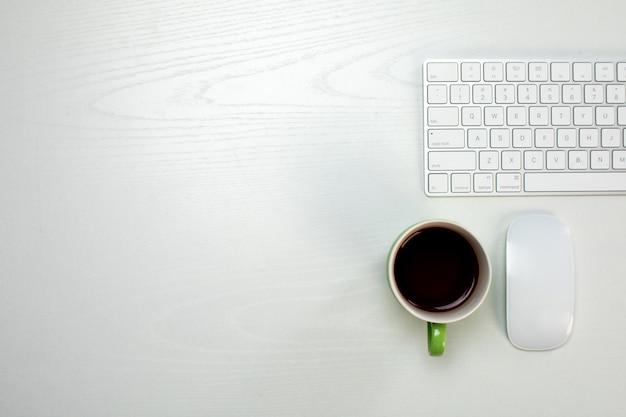 一杯のコーヒーとワイヤレスキーボードとマウス
