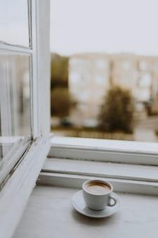 창문 옆에있는 커피 한 잔