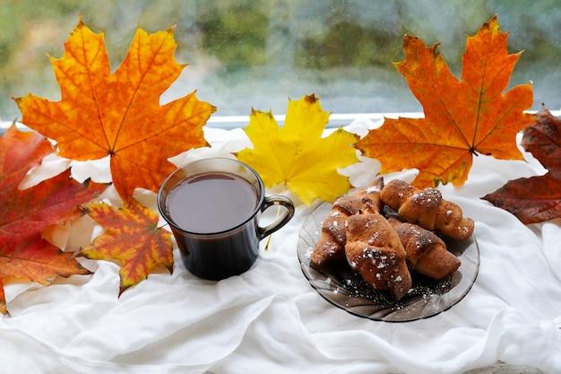 一杯のコーヒーカプチーノ、クロワッサン、紅葉が窓辺にとどまります。秋の装飾、秋の気分、秋の静物