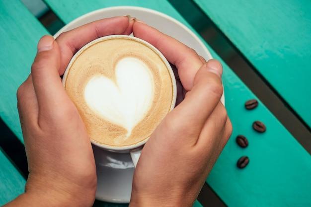 녹색 테이블에 하트가 있는 커피 카푸치노 한 잔. 낭만적인 아침과 아침 식사의 개념 프리미엄 사진