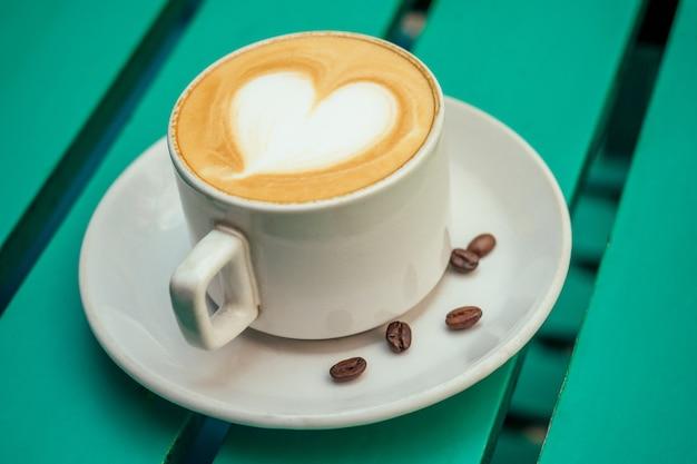 녹색 테이블에 하트가 있는 커피 카푸치노 한 잔. 낭만적인 아침과 아침 식사의 개념