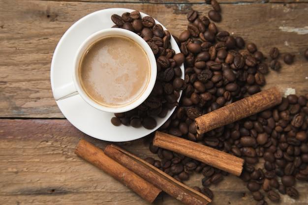 一杯のコーヒー、コーヒーの種、シナモン、木製のテーブルの上の本
