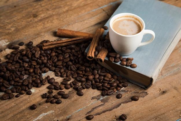 커피, 커피 씨앗, 계피, 나무 테이블에 책 한 잔