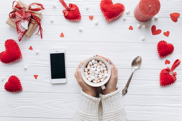 Чашка кофе, декоративные сердца, подарки и смартфон на белом столе для дня святого валентина