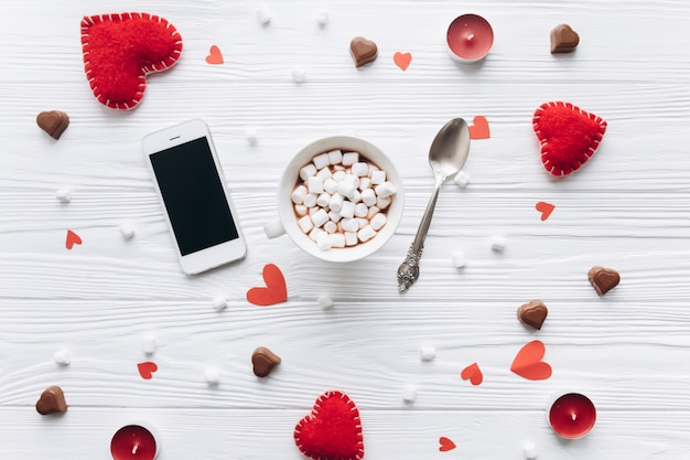 Чашка кофе, декоративные сердца, подарки и смартфон на белом столе для валентина