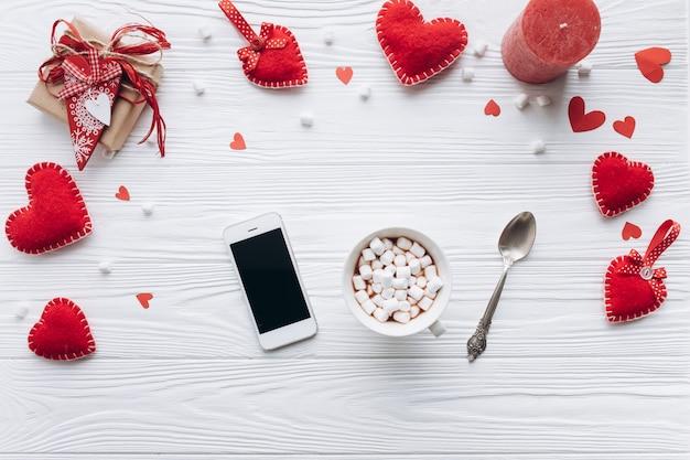 Чашка кофе, декоративные сердца, подарки и смартфон на белом столе