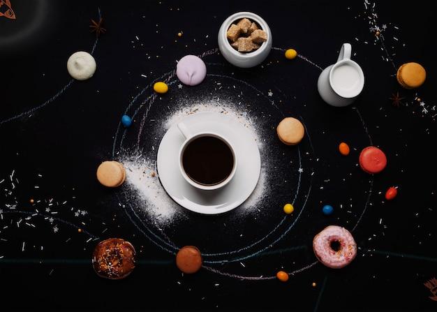 一杯のコーヒー、ドーナツ、マカロン、砂糖、ミルククリームの水差し、黒い背景のケーキはコーヒーシステムのように見えます