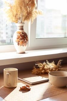 一杯のコーヒー、ドライフラワー、バランキス、木製のテーブルのメモ帳。ブラウンとホワイト。