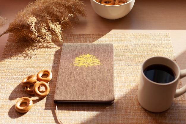Чашка кофе, сухие цветы, баранкис, блокнот на деревянном столе.