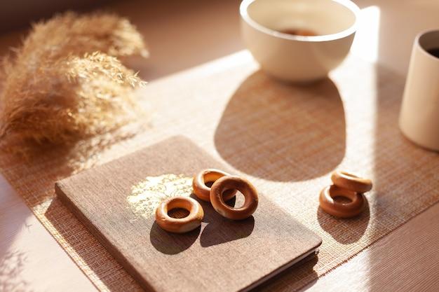 一杯のコーヒー、ドライフラワー、バランキス、木製のテーブルのメモ帳。