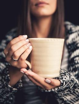 美しい女性の手と美しい唇に一杯のコーヒー