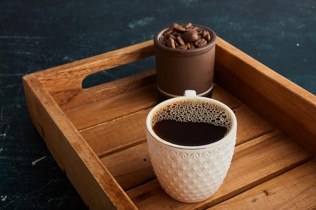 Чашка кофе на деревянном подносе.