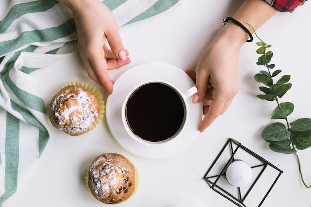 Чашка кофе в руках и кексы на белой поверхности и кексы