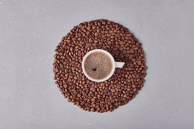 Чашка кофе в мягкой смеси зерен арабики.