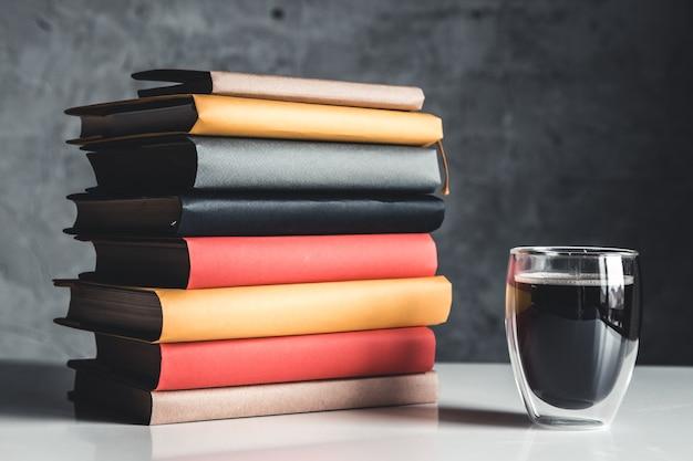 灰色の背景の本のスタックの近くに一杯のコーヒー