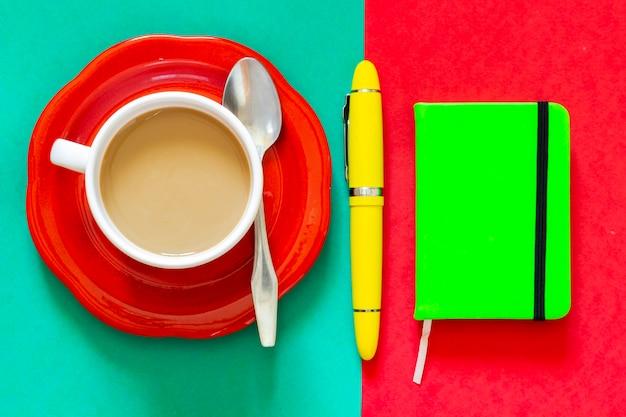 緑のノートと黄色の万年筆の横にある一杯のコーヒー。朝食からメモを取ったり、一日を整理したりする準備ができています。
