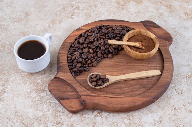 コーヒー豆と挽いたコーヒーパウダーのトレイの横にある一杯のコーヒー