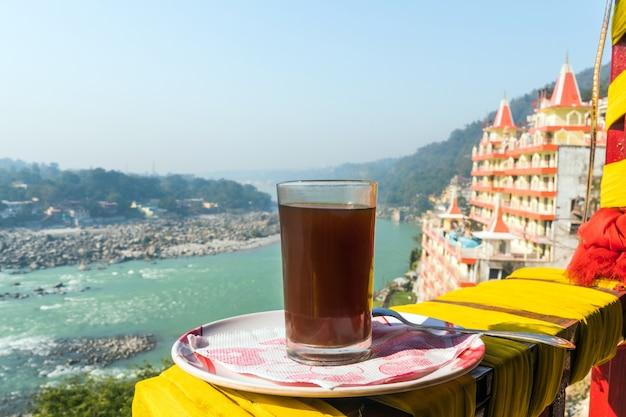 リシケシの街の美しい背景にコーヒーを一杯。ヒマラヤ山脈で早朝に観光インドの朝食。