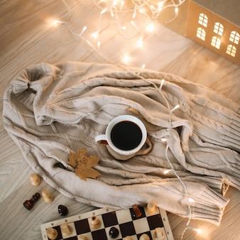 Чашка кофе на вязаном бежевом пледе с огнями боке