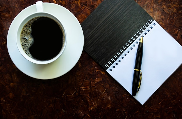 Чашка кофе на блюдце рядом с блокнотом с ручкой работа начинается с завтрака