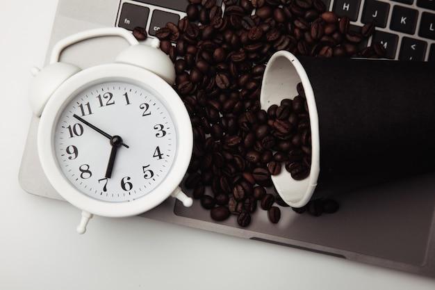 Чашка кофе на клавиатуре, будильник и крупный план кофейных зерен.