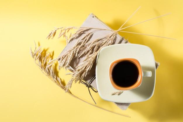 오래 된 책에 커피 한 잔과 노란색과 가혹한 빛의 마른 옥수수 귀. 건강, 조화, 포용성. 공간을 복사하십시오. 평면도