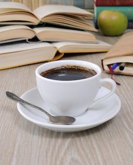 Чашка кофе на столе на фоне открытой книги с блокнотом