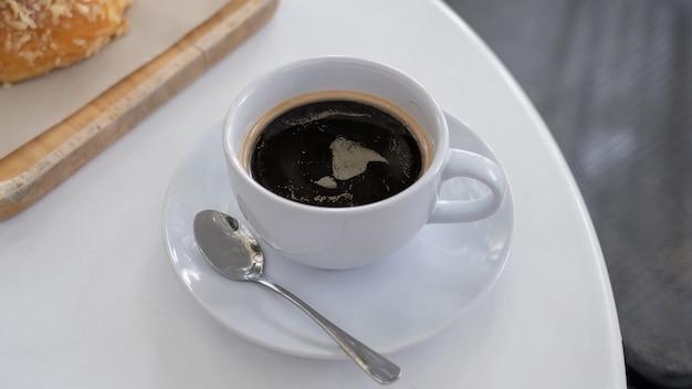 仕事の休憩時間、食品のコンセプトと白いテーブルの上のコーヒーのカップ。熱いエスプレッソミックスのグラスのクローズアップコピースペースのあるソフトドリンク