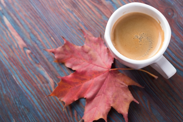 Чашка кофе на деревянный стол с опавших листьев. copyspace
