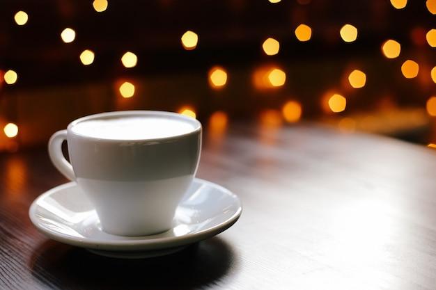 背景のライトと木製のテーブルの上のコーヒーカップ