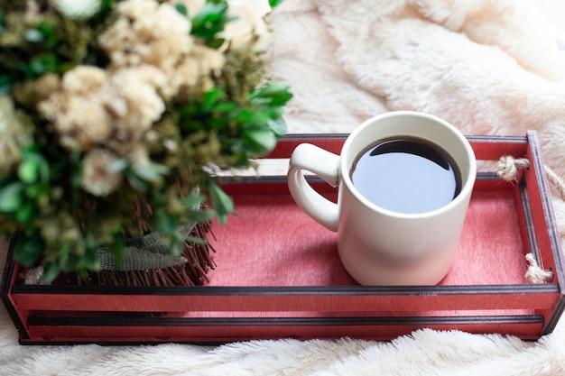一杯のコーヒーまたは紅茶、ドライフラワー、ベージュの毛布の上に赤い木箱。