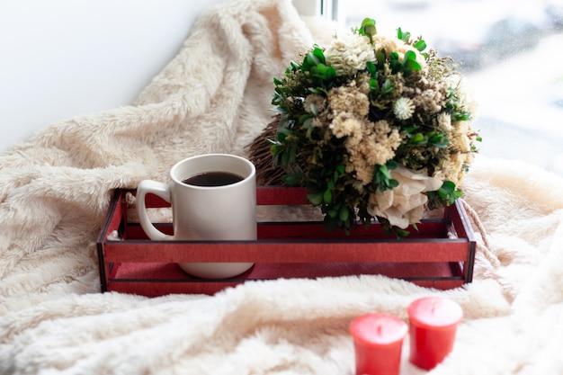 一杯のコーヒーまたは紅茶、ドライフラワー、白、赤のキャンドル、ベージュの毛布の上に赤い木箱。