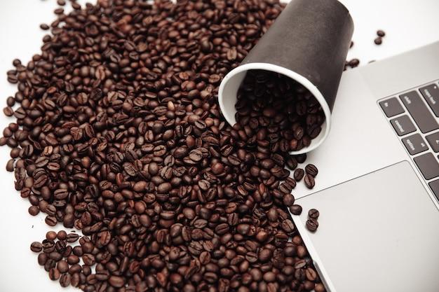 Чашка кофе на стол на ноутбуке и коричневые кофейные зерна.