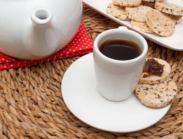 쌀 쿠키와 커피 포트로 가득 찬 그릇에 둘러싸인 밀짚 테이블 아래 커피 한 잔
