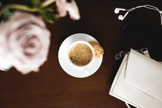 柔らかいアネモネの花束、ユーカリの枝、パステルパープルのバラ、女性のハンドバッグ、ヘッドフォン、茶色の木製テーブルに電話を置いた一杯のコーヒー。
