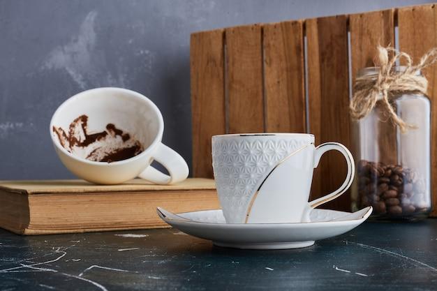 空のコーヒーを脇に置いた一杯のコーヒー。