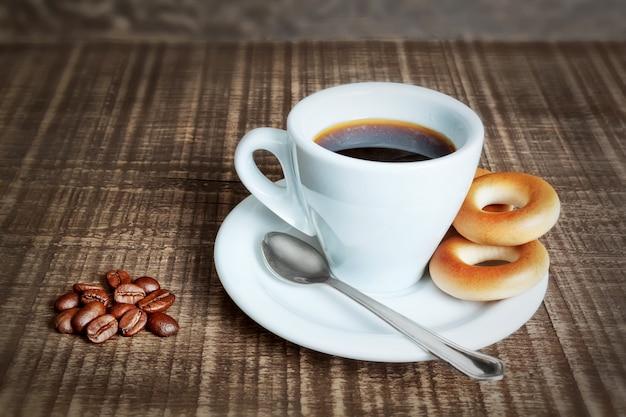 焼きたてのクラッカー、ベーグルとコーヒーのカップ。木製のテーブルの上のコーヒー豆