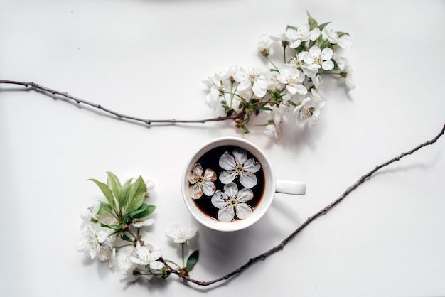 桜の枝が咲く一杯のコーヒー