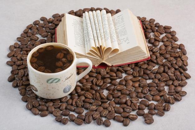 책과 흰색 배경에 원두 커피와 커피 한잔. 고품질 사진