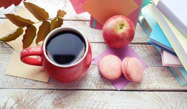 ケーキとコーヒーのカップは、窓際の木製のテーブルに家の快適さの概念を残します