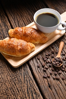 Чашка кофе с кофе в зернах и круассан на деревянный стол