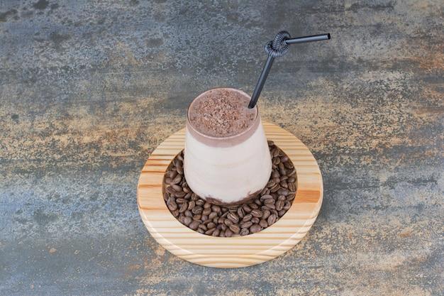 木の板にコーヒー豆とコーヒーのカップ。高品質の写真
