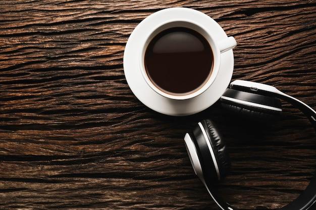 Чашка кофе с наушниками на деревянном столе. вид сверху кофе с копией пространства. концепция напитка.