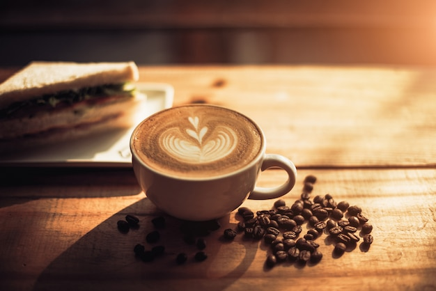 나무 테이블 배경에 흰색 컵과 샌드위치에 하트 패턴으로 커피 한 잔