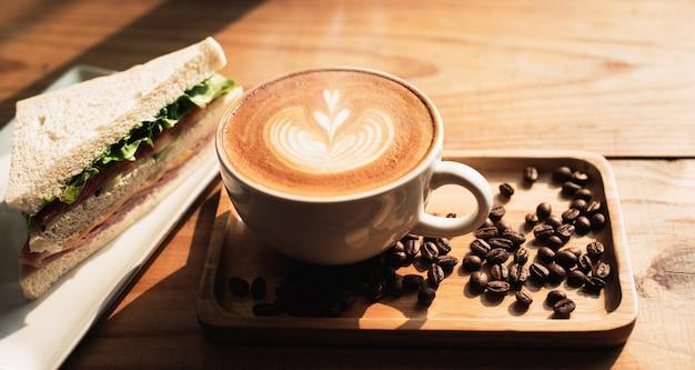 Чашка кофе с рисунком сердца в белой чашке и бутерброд на фоне деревянный стол